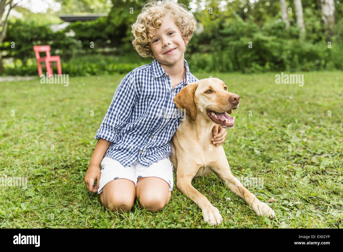 Portrait of boy sitting with dog in garden Stock Photo