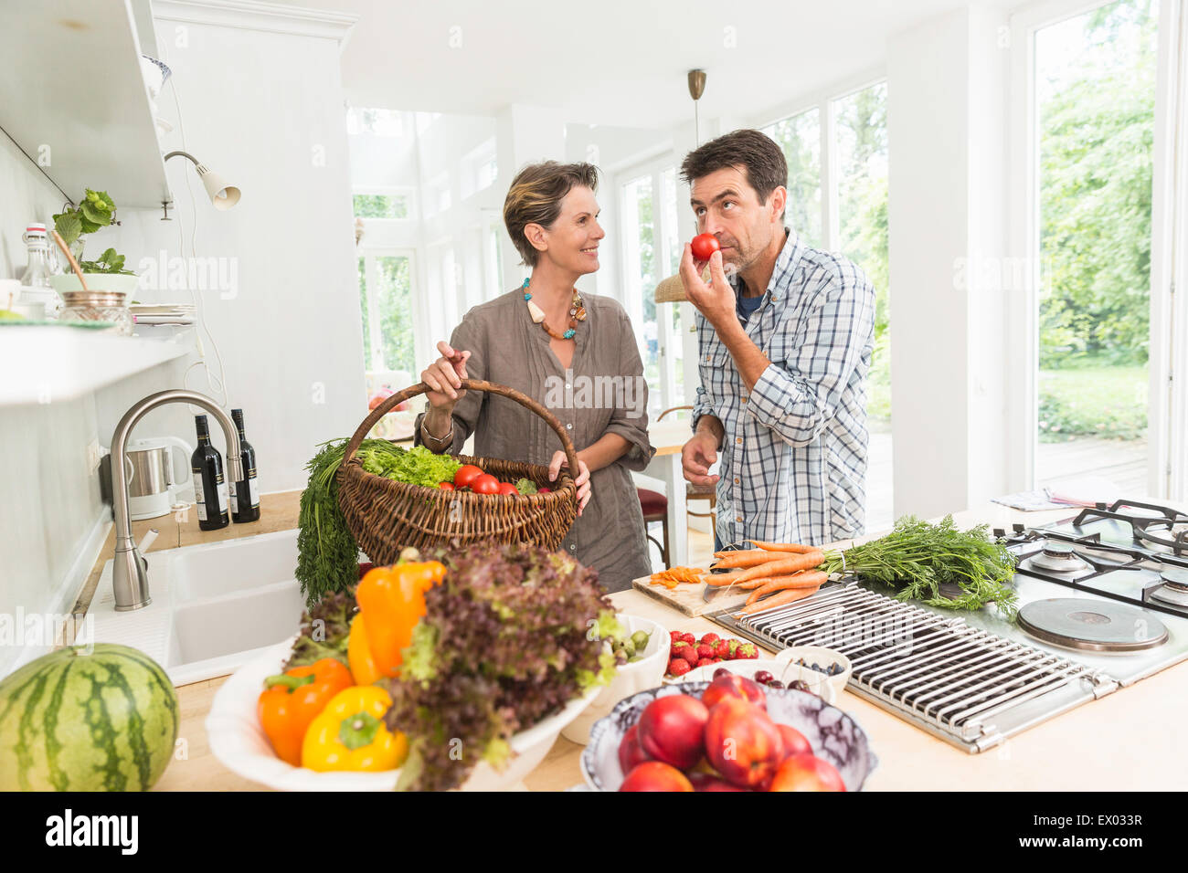 Couple in kitchen preparing fresh vegetables - Stock Image