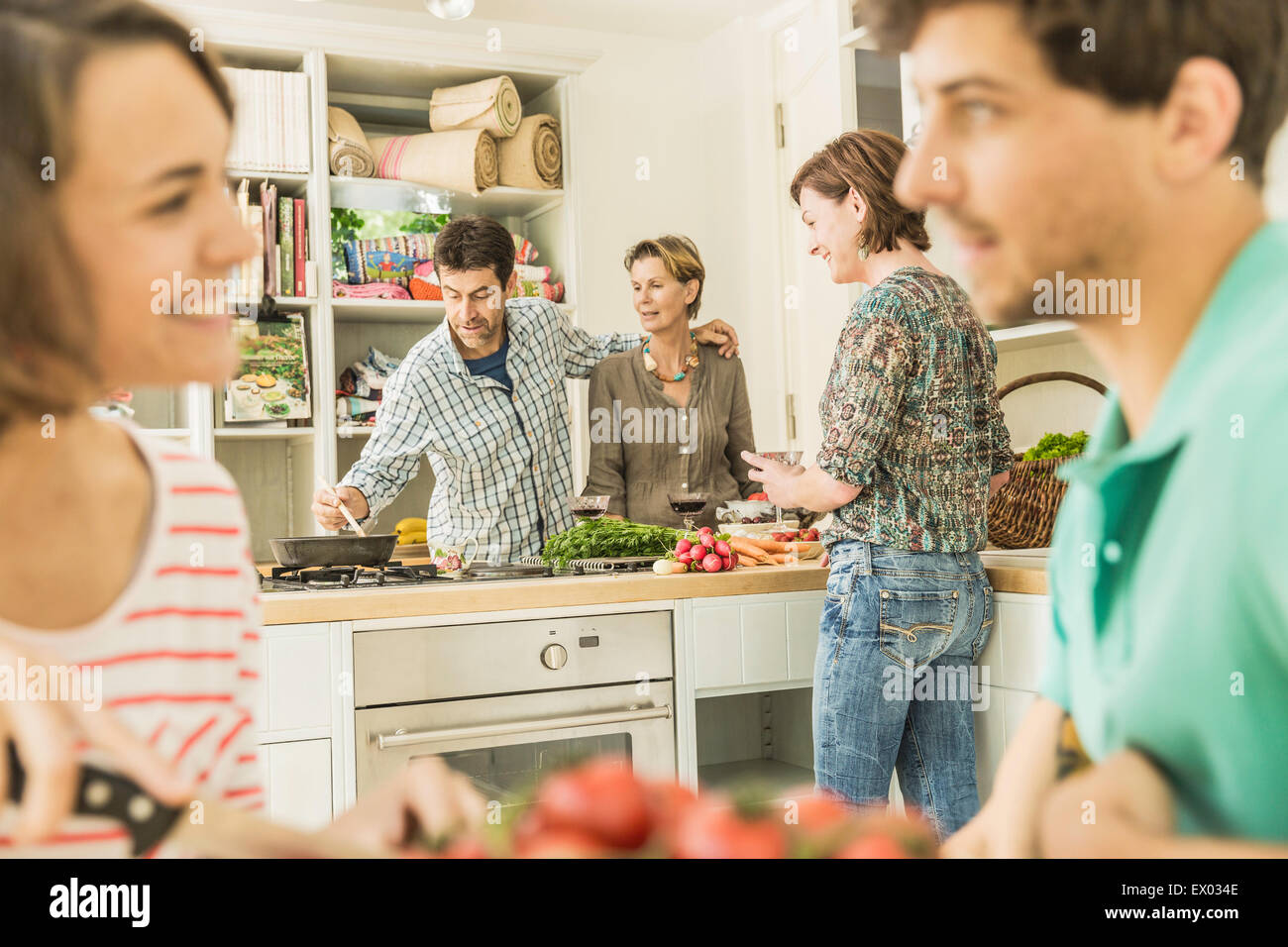 Five adult friends gathering for dinner party in kitchen - Stock Image