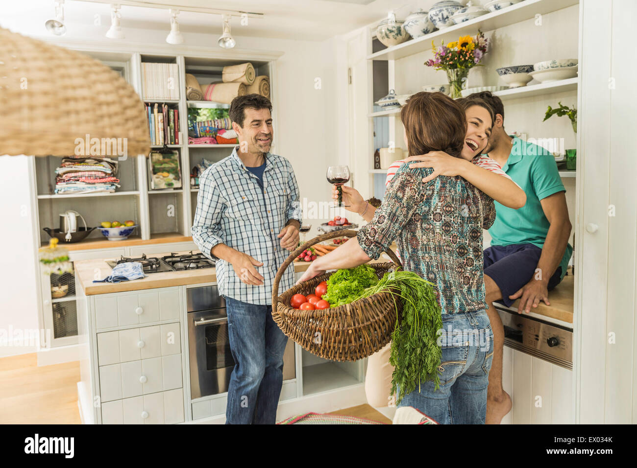 Four adult friends greeting in kitchen - Stock Image