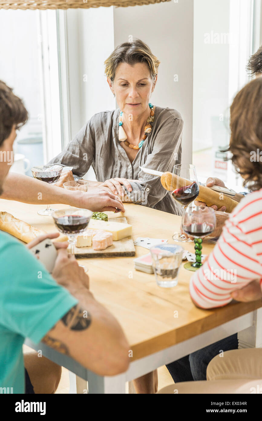 Adult friends playing cards and drinking wine at dining table - Stock Image