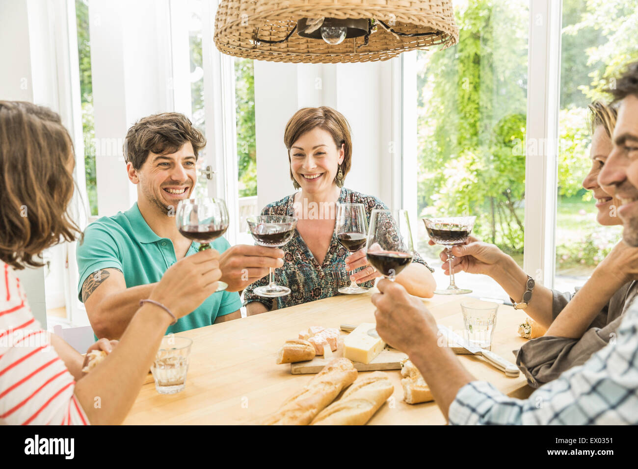 Five adult friends making a toast at dining table Stock Photo