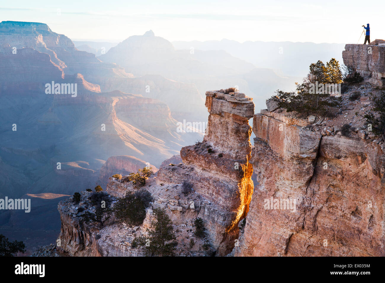 Distant silhouetted view of woman taking photographs of Grand Canyon, Arizona, USA - Stock Image