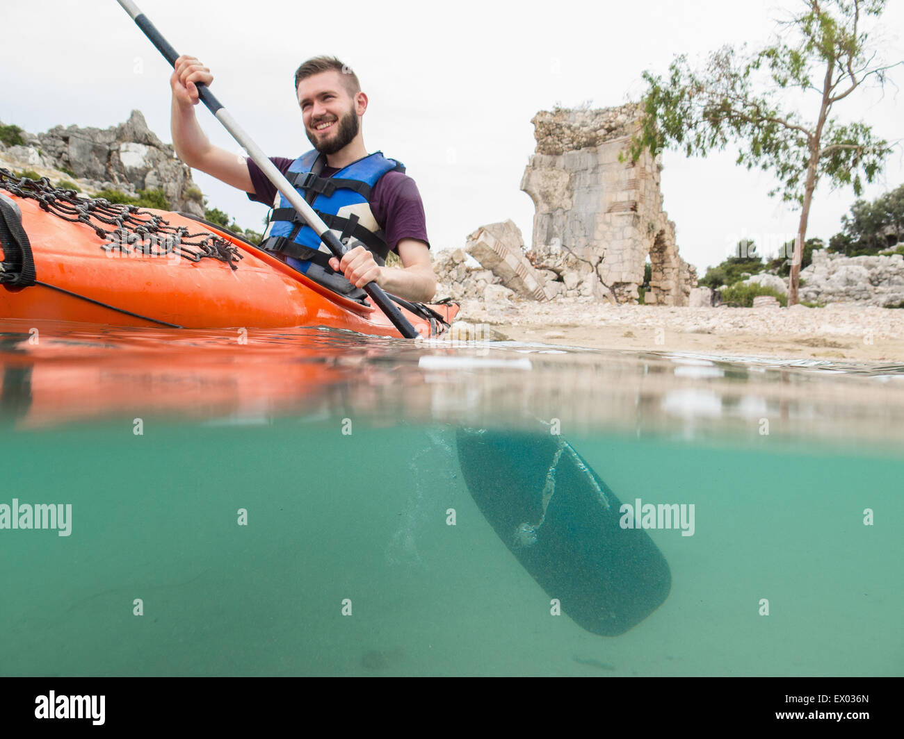Man kayaking near ancient ruins, Lycian Way, Turkey - Stock Image
