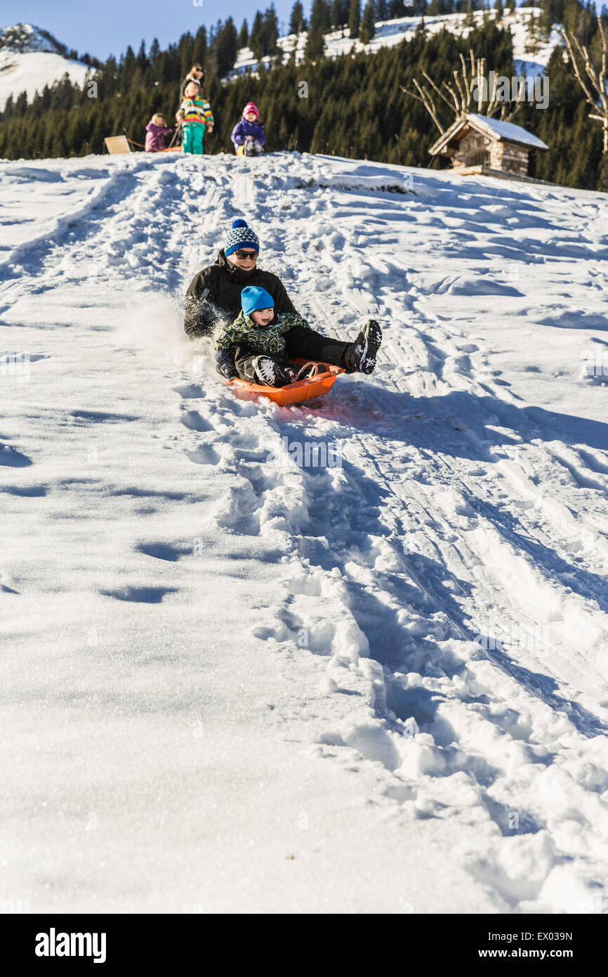 Father and son riding sled down snow-covered slope, Achenkirch, Tirol, Austria - Stock Image