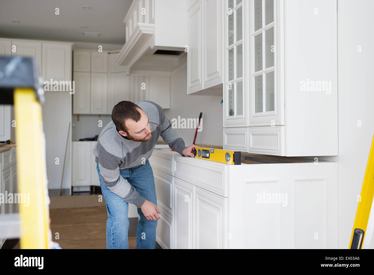 Carpenter installing kitchen cabinet - Stock Image