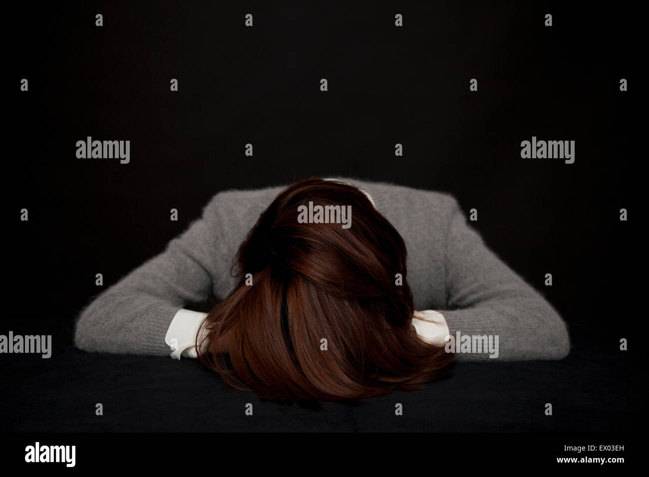 Portrait of woman resting head on table - Stock Image