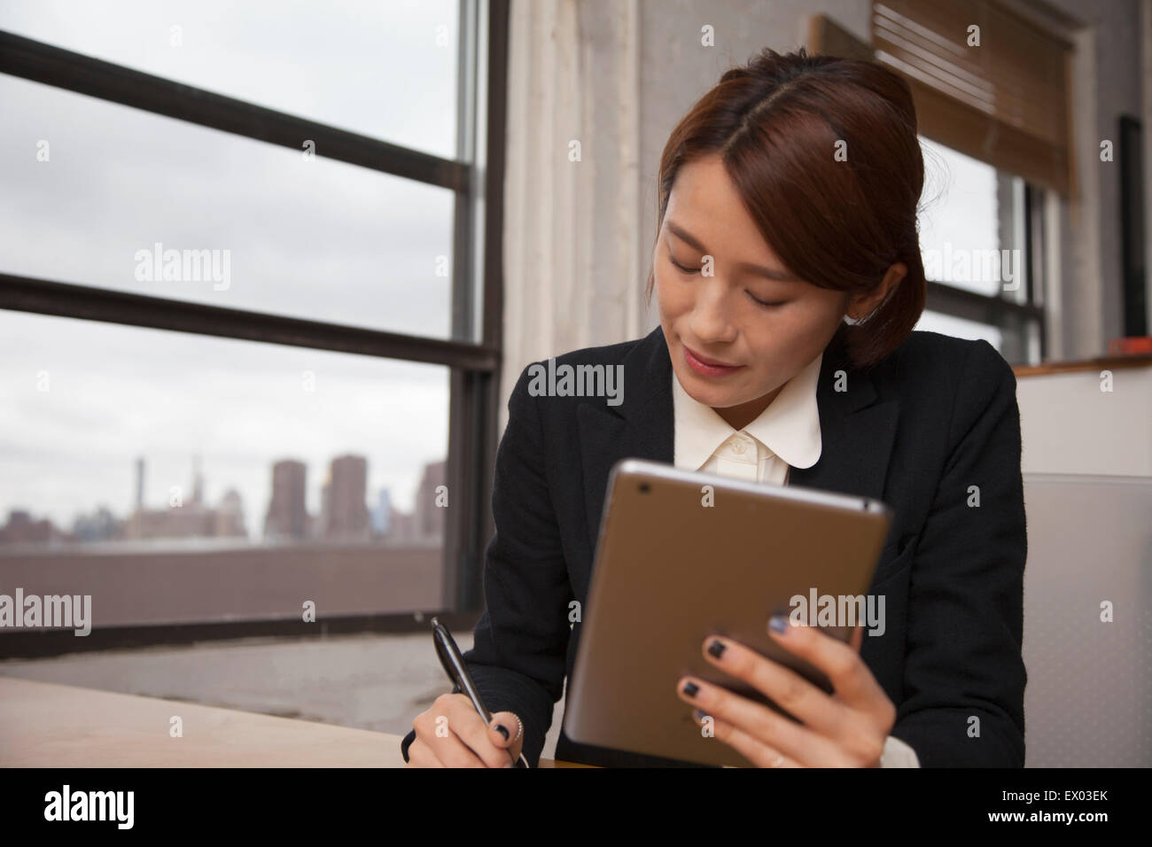 Businesswoman holding digital tablet and writing notes - Stock Image