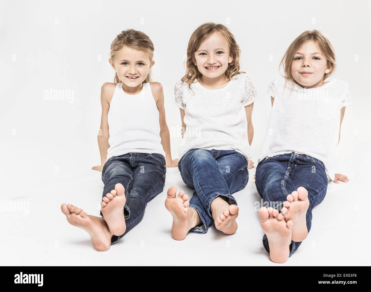 Portrait of girls with legs outstretched - Stock Image