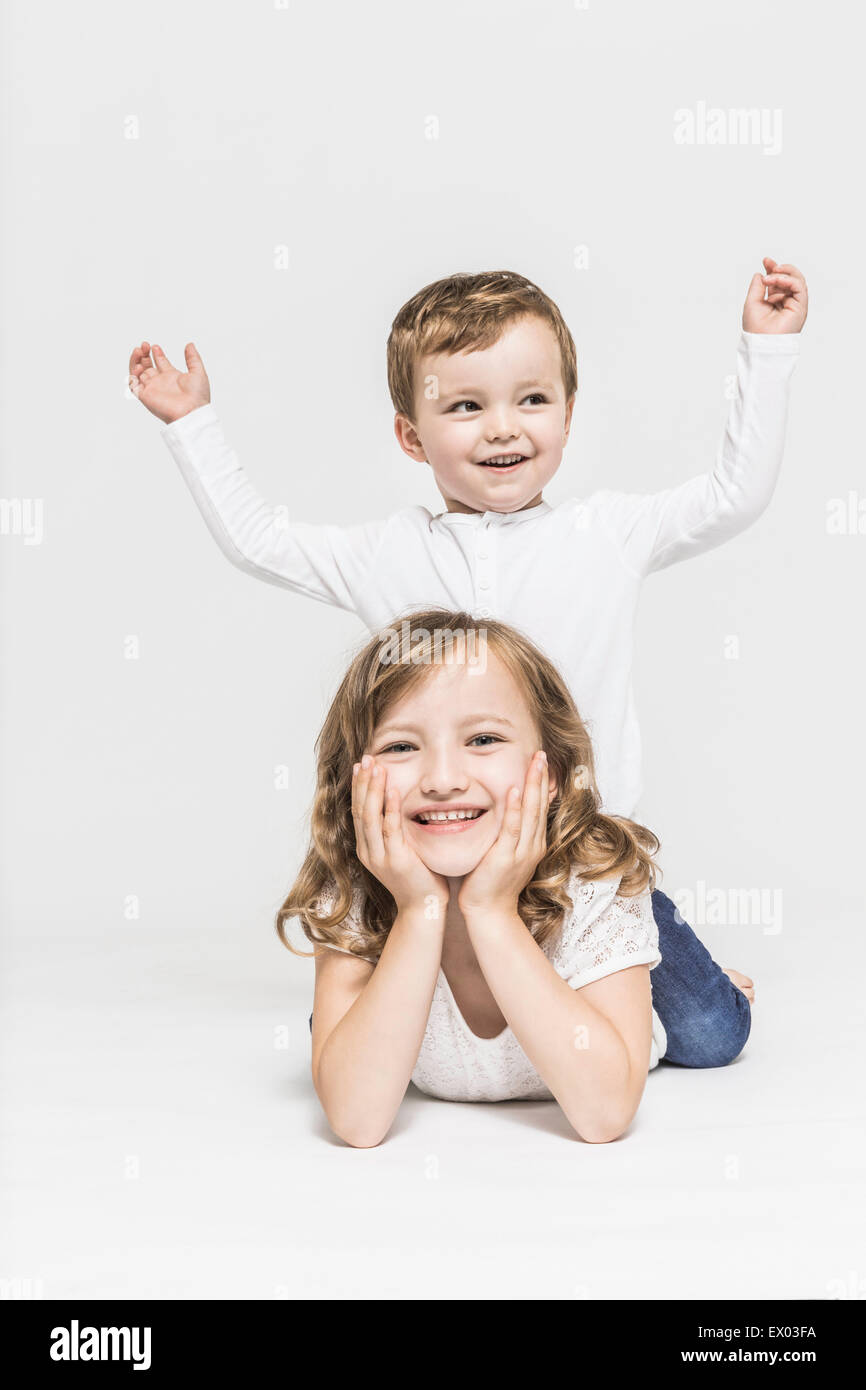 Brother and sister lying on stomach - Stock Image