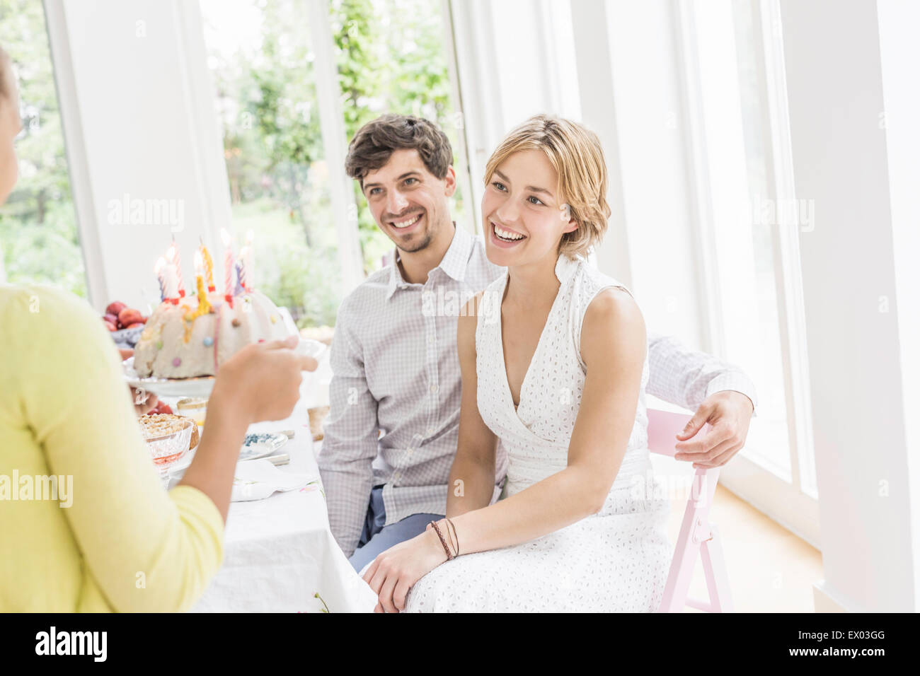 Girl handing birthday cake to parents at birthday party - Stock Image