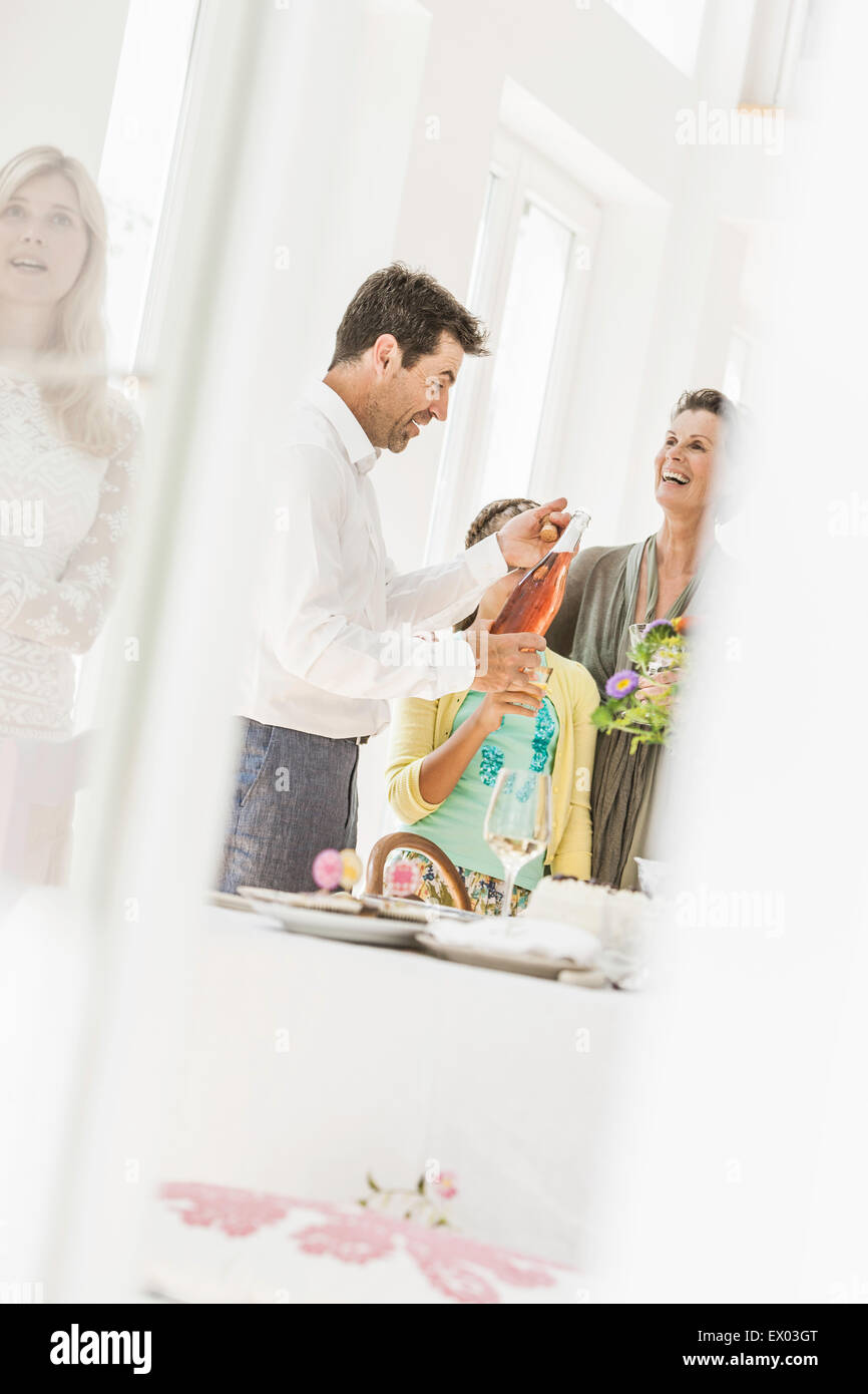 Mature man with wine bottle at family party - Stock Image