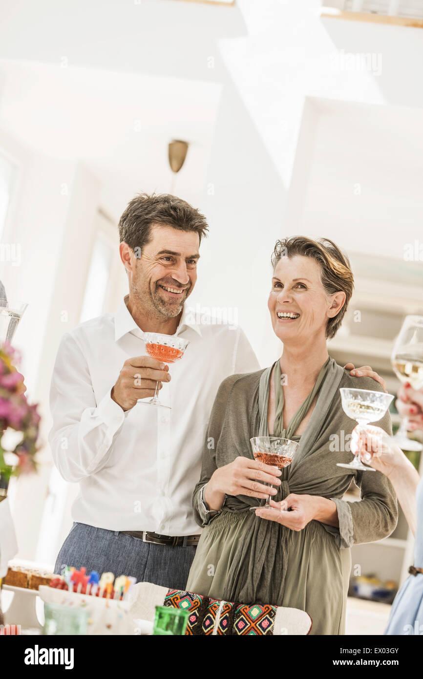 Family toasting senior woman at birthday party - Stock Image