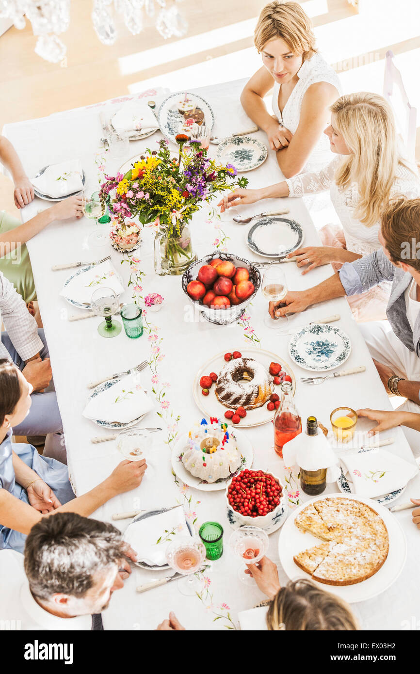 Overhead view of family at birthday party in dining room - Stock Image