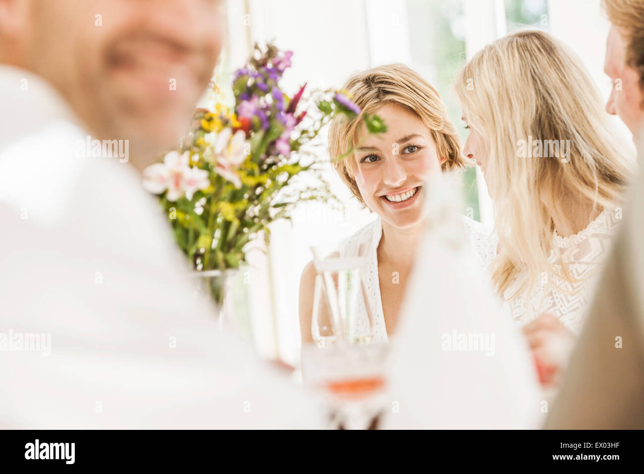 Adults chatting at family birthday party - Stock Image
