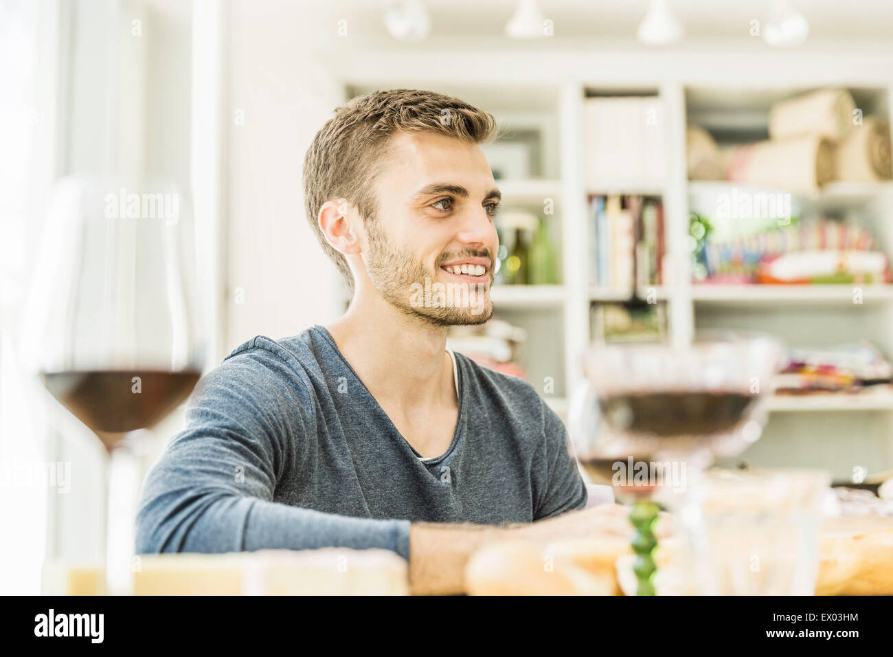 Young man drinking wine at table in dining room - Stock Image