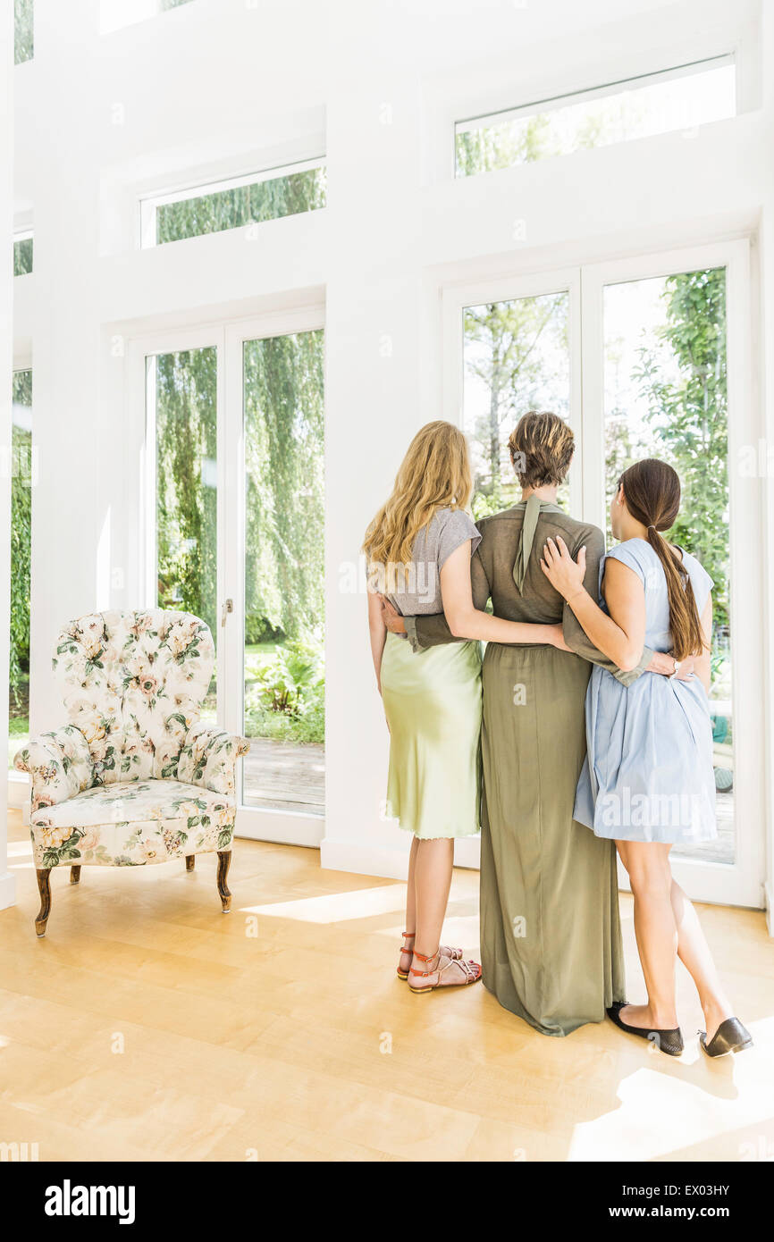 Senior woman and two adult daughters looking out of window in living room - Stock Image
