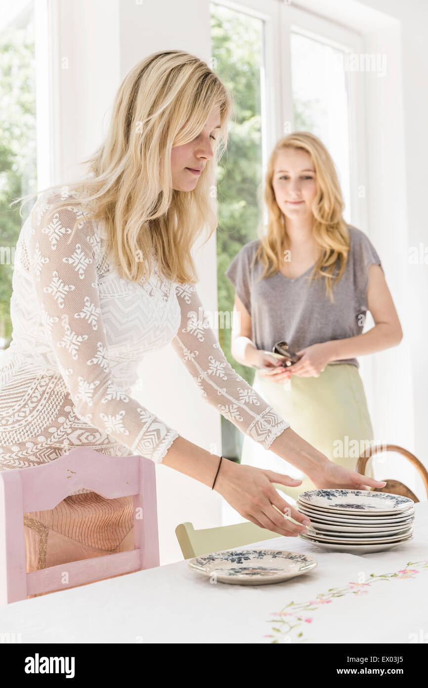 Adult sisters laying dining room table - Stock Image
