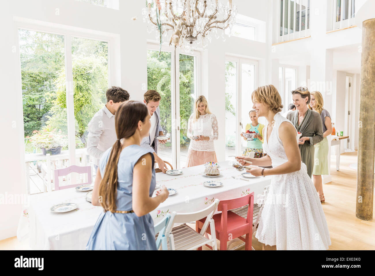 Family team preparing dining room for birthday party - Stock Image