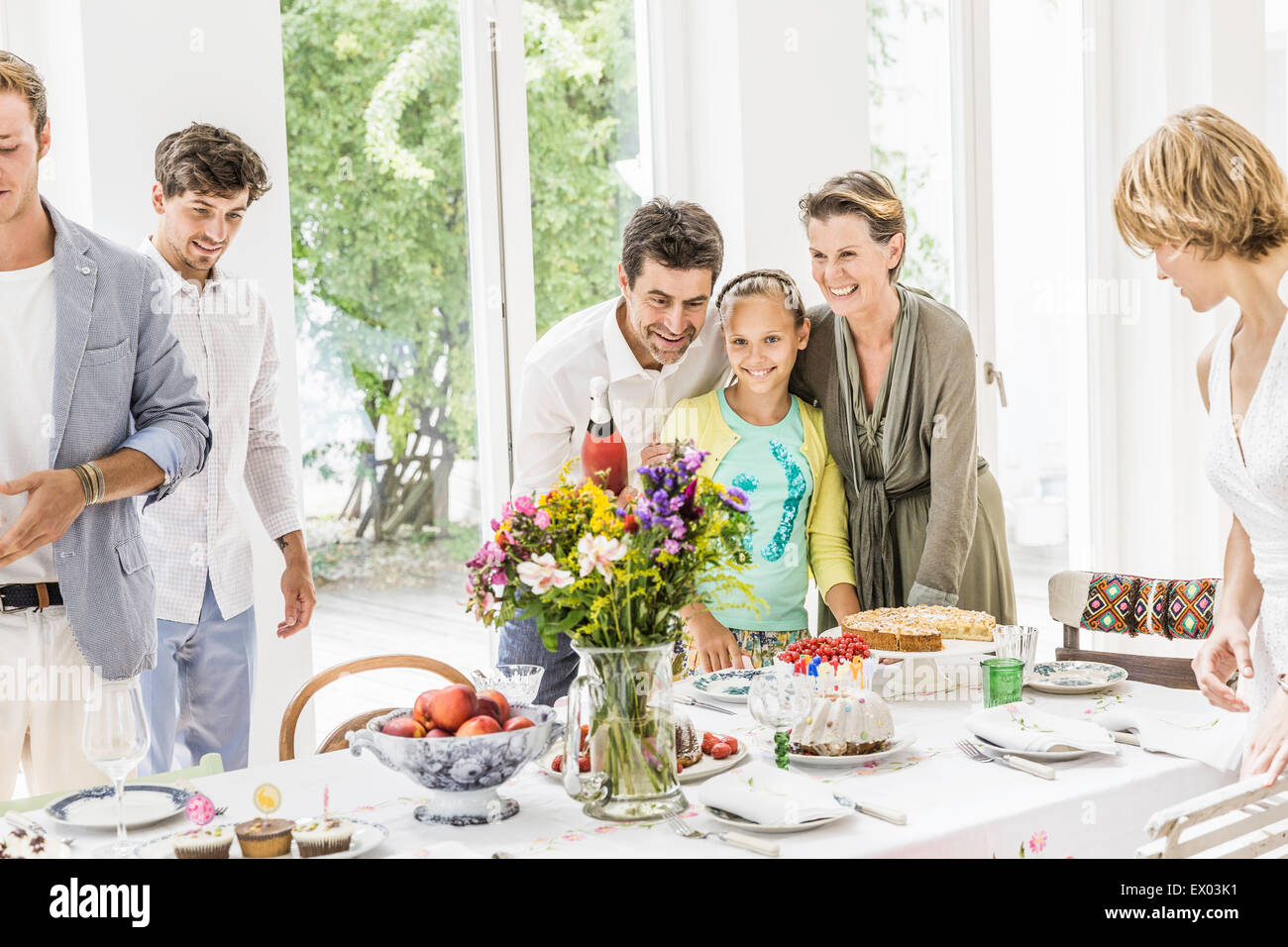 Family preparing champagne for party in dining room Stock Photo