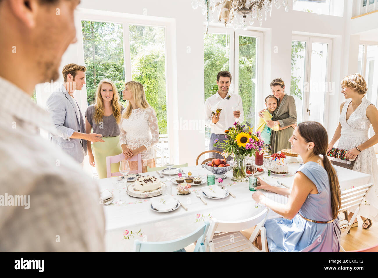Family chatting around party table  in dining room Stock Photo