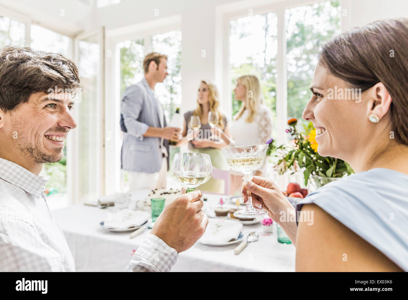Young couple making champagne toast at family birthday party - Stock Image