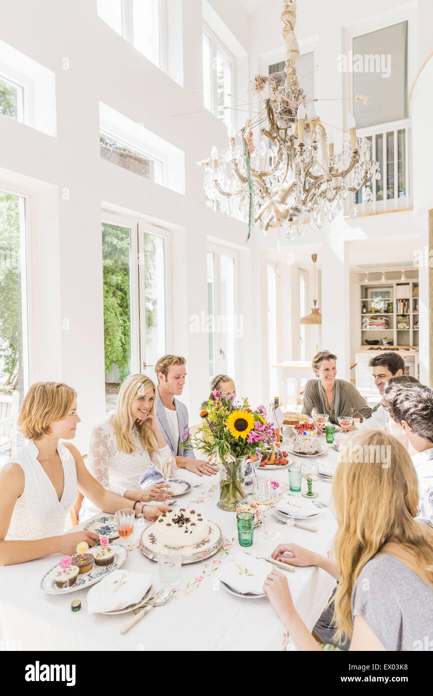 Family sitting around table at birthday party - Stock Image