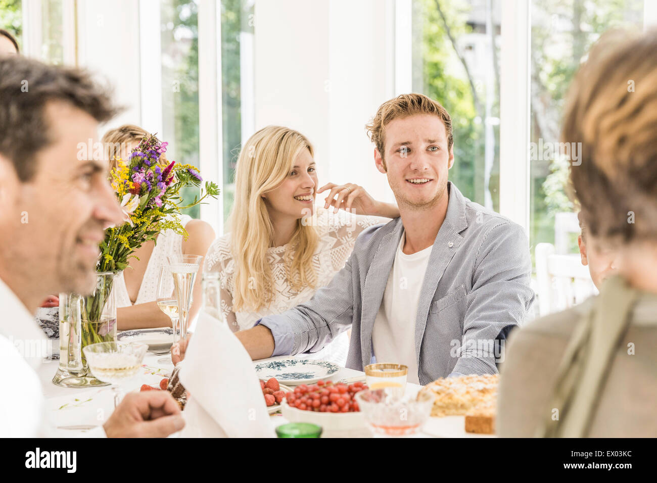 Family adults chatting at birthday party table - Stock Image