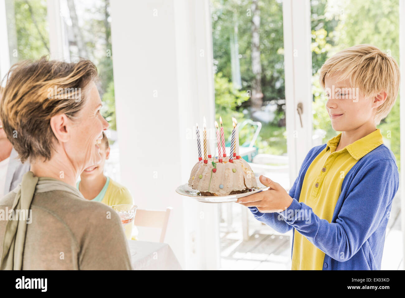 Boy handing birthday cake to grandmother in dining room - Stock Image