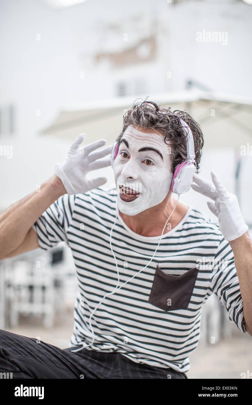 Male mime artist listening to headphones, Ibiza, Spain - Stock Image