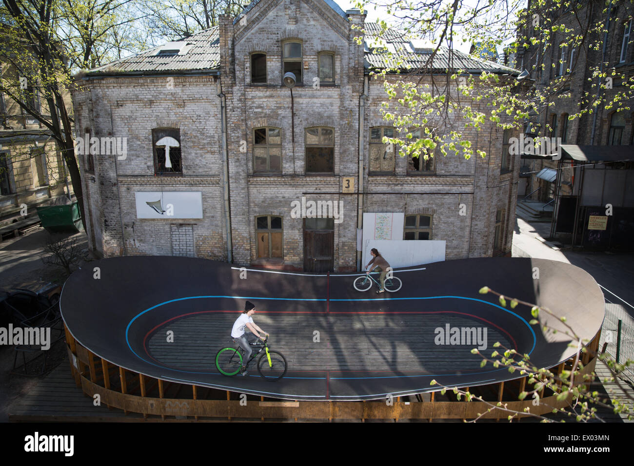 High angle view of two cyclists racing around city velodrome, Riga, Latvia - Stock Image