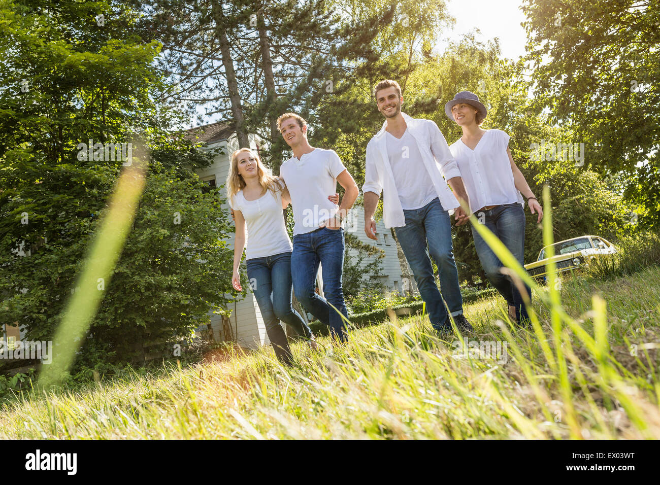 Group of people walking through forest Stock Photo
