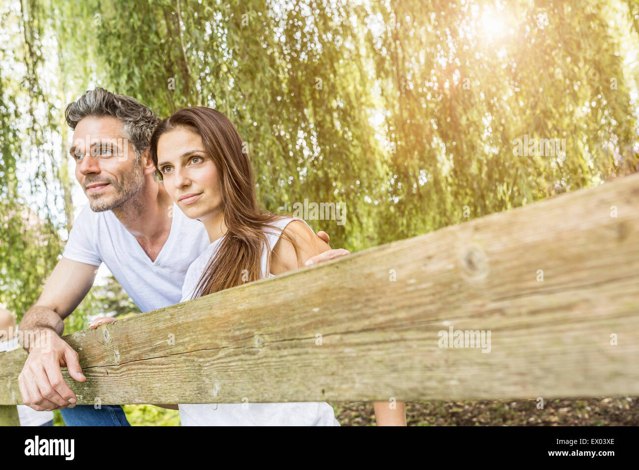 Portrait of couple standing behind fence in forest - Stock Image