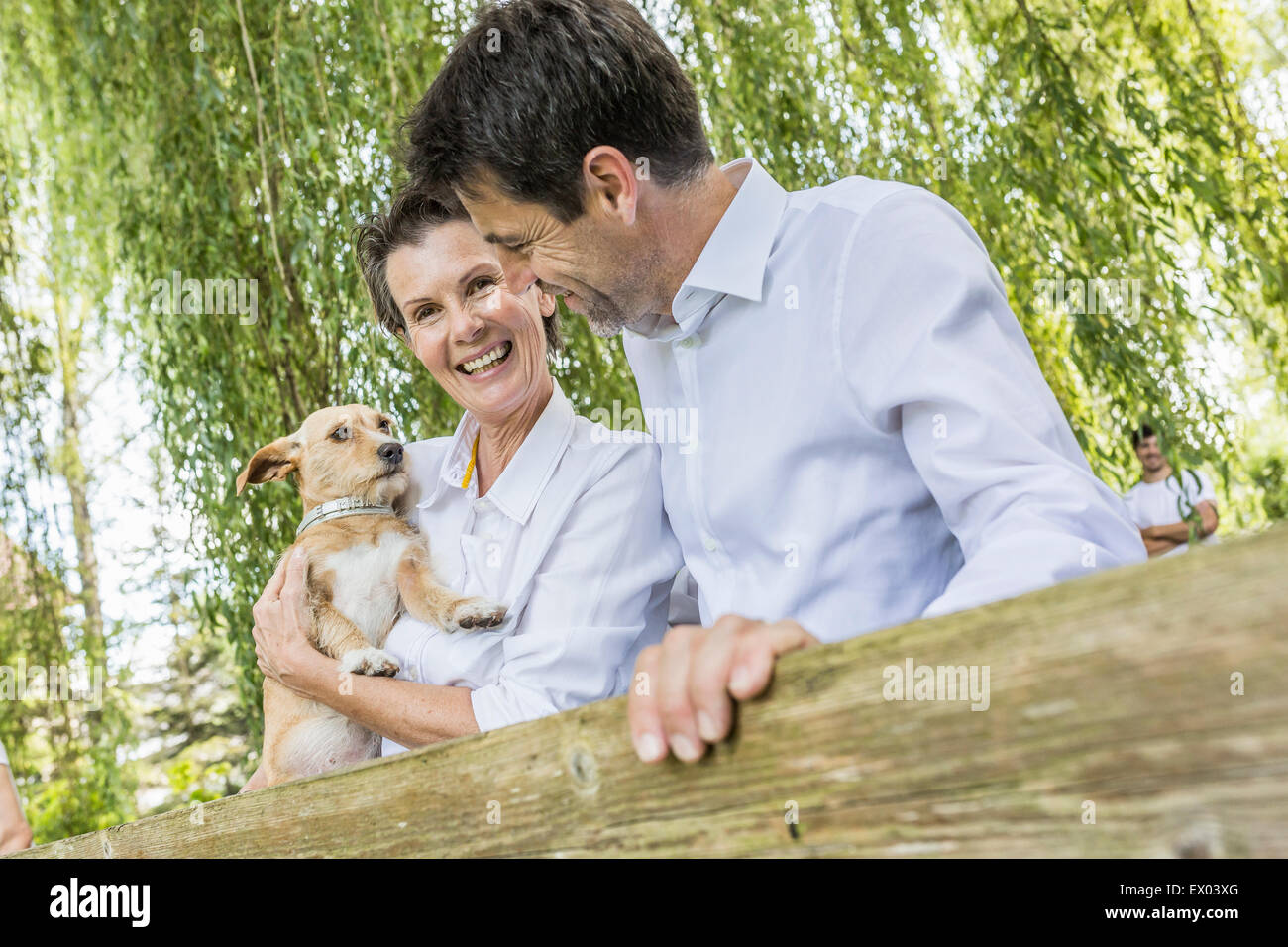 Portrait of couple with pet dog, standing by fence in forest - Stock Image