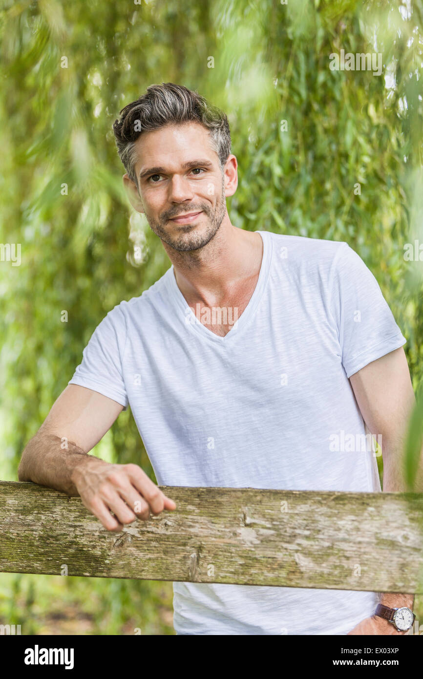 Portrait of mid adult man leaning on fence in forest - Stock Image