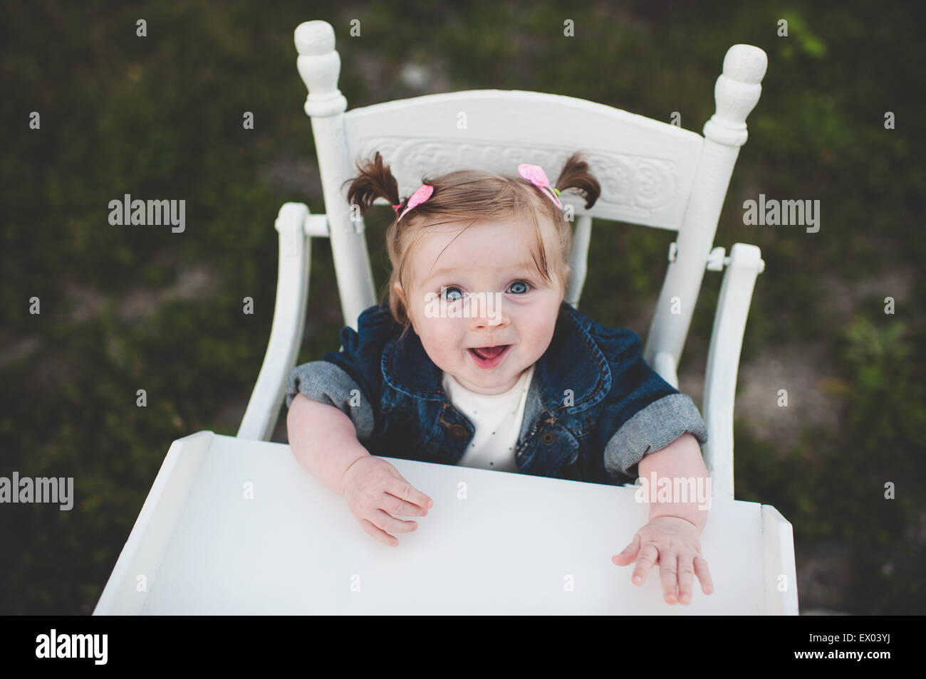 Portrait of baby girl in high chair - Stock Image