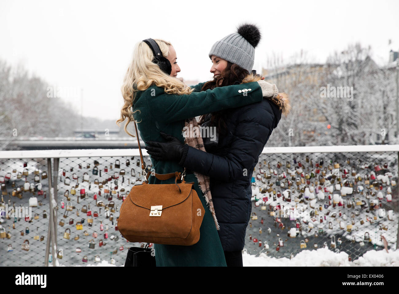 Two mid adult women hugging on bridge - Stock Image