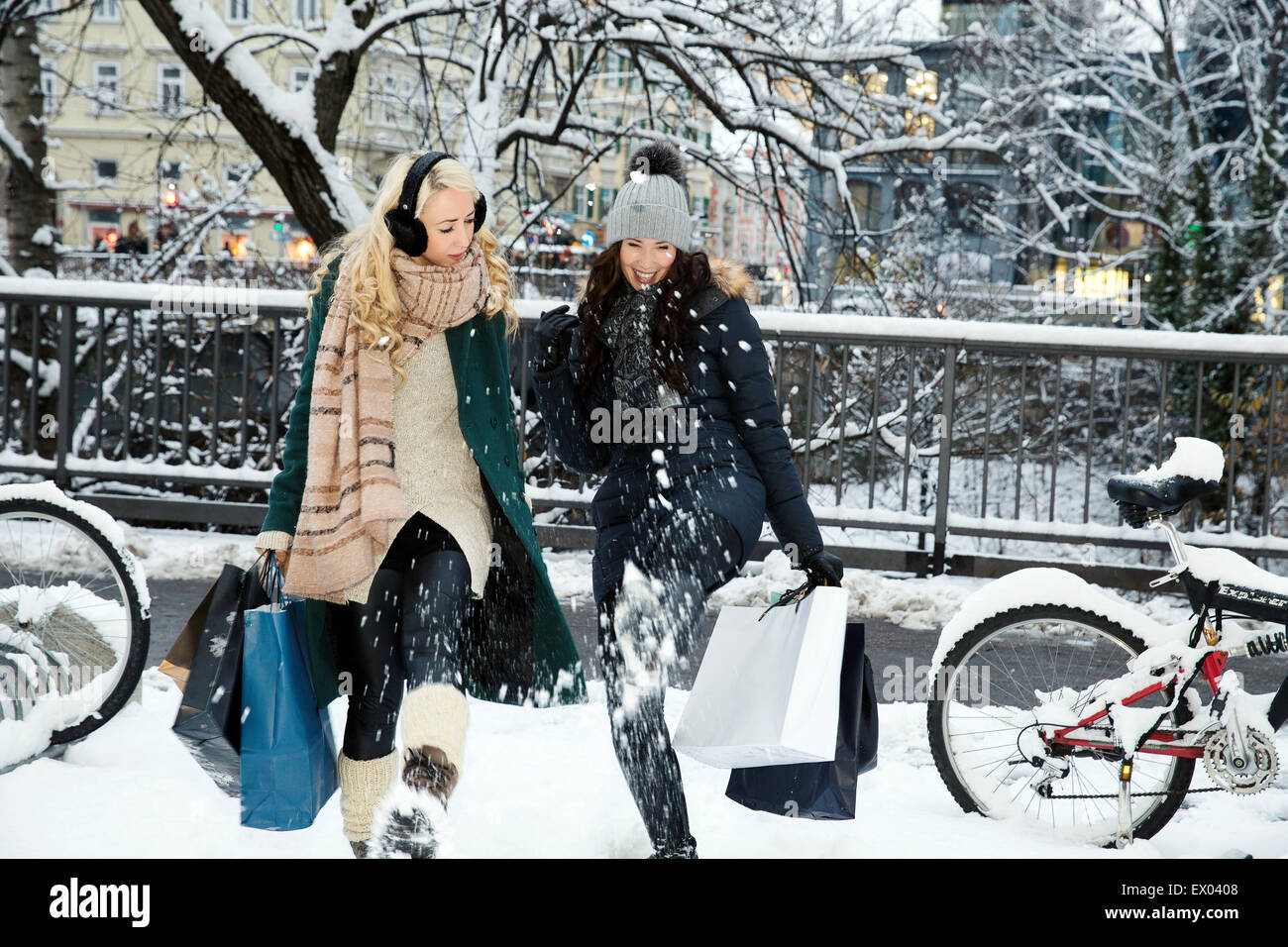 Two mid adult women in snow with shopping bags - Stock Image