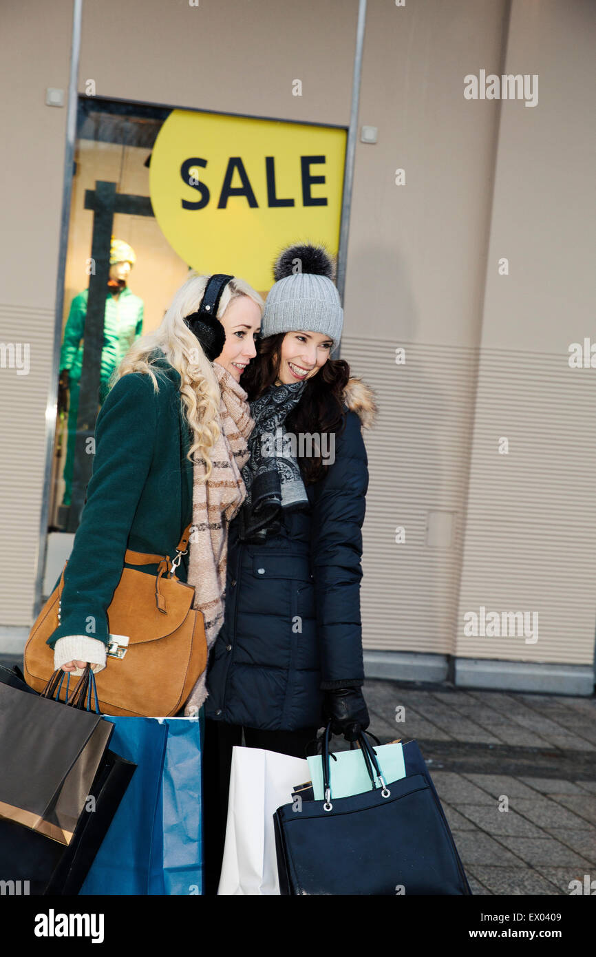 Two mid adult women with shopping bags in winter sales - Stock Image