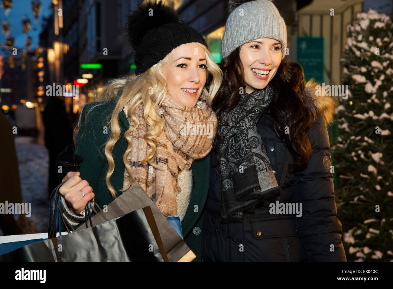 Two mid adult women wearing hats, shopping - Stock Image