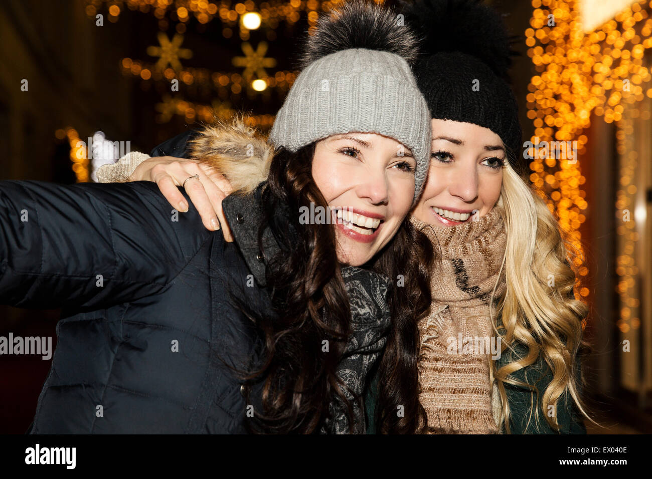 Two mid adult women wearing hats, smiling - Stock Image