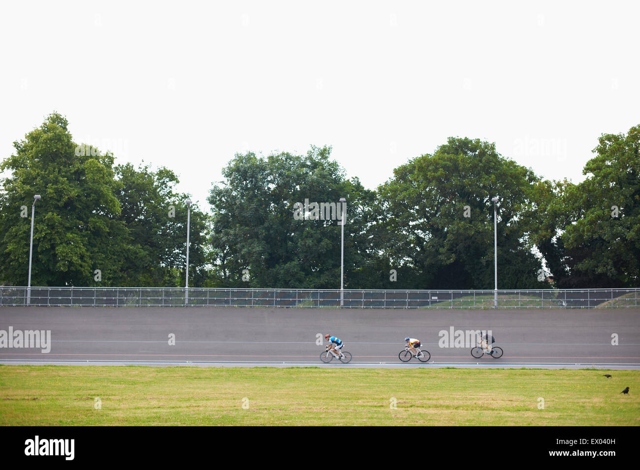 Three cyclists cycling on track at velodrome, outdoors Stock Photo