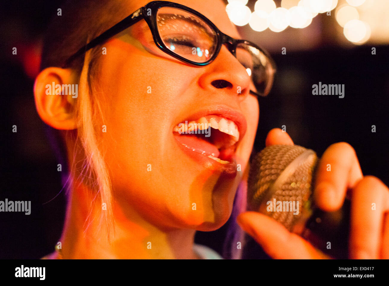 Punk girl singing into microphone, close-up - Stock Image