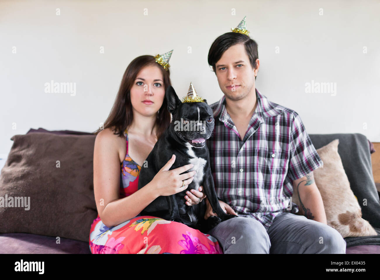 Portrait of couple sitting on sofa with dog and deadpan expressions - Stock Image
