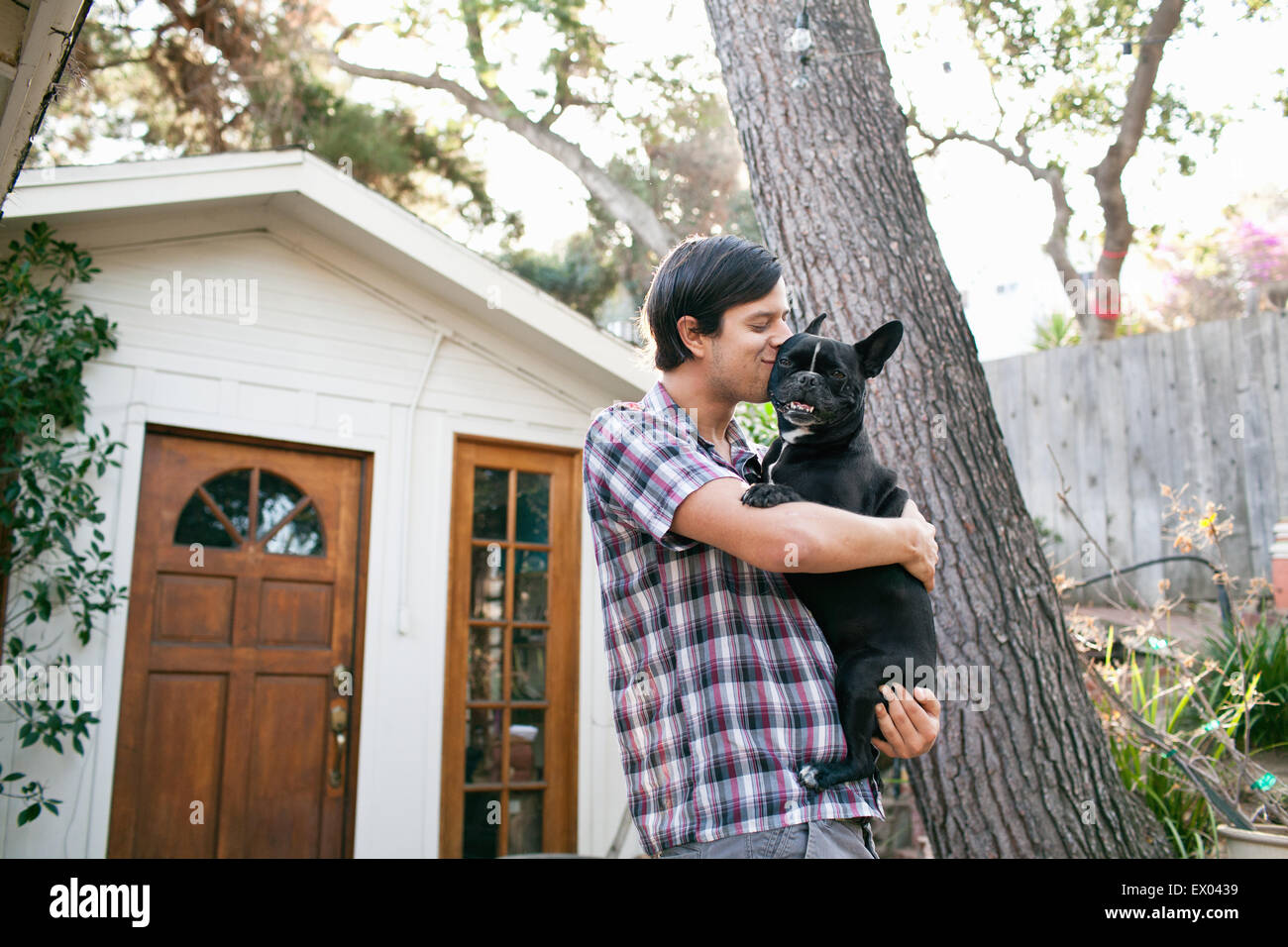 Young man kissing dog outside front door - Stock Image