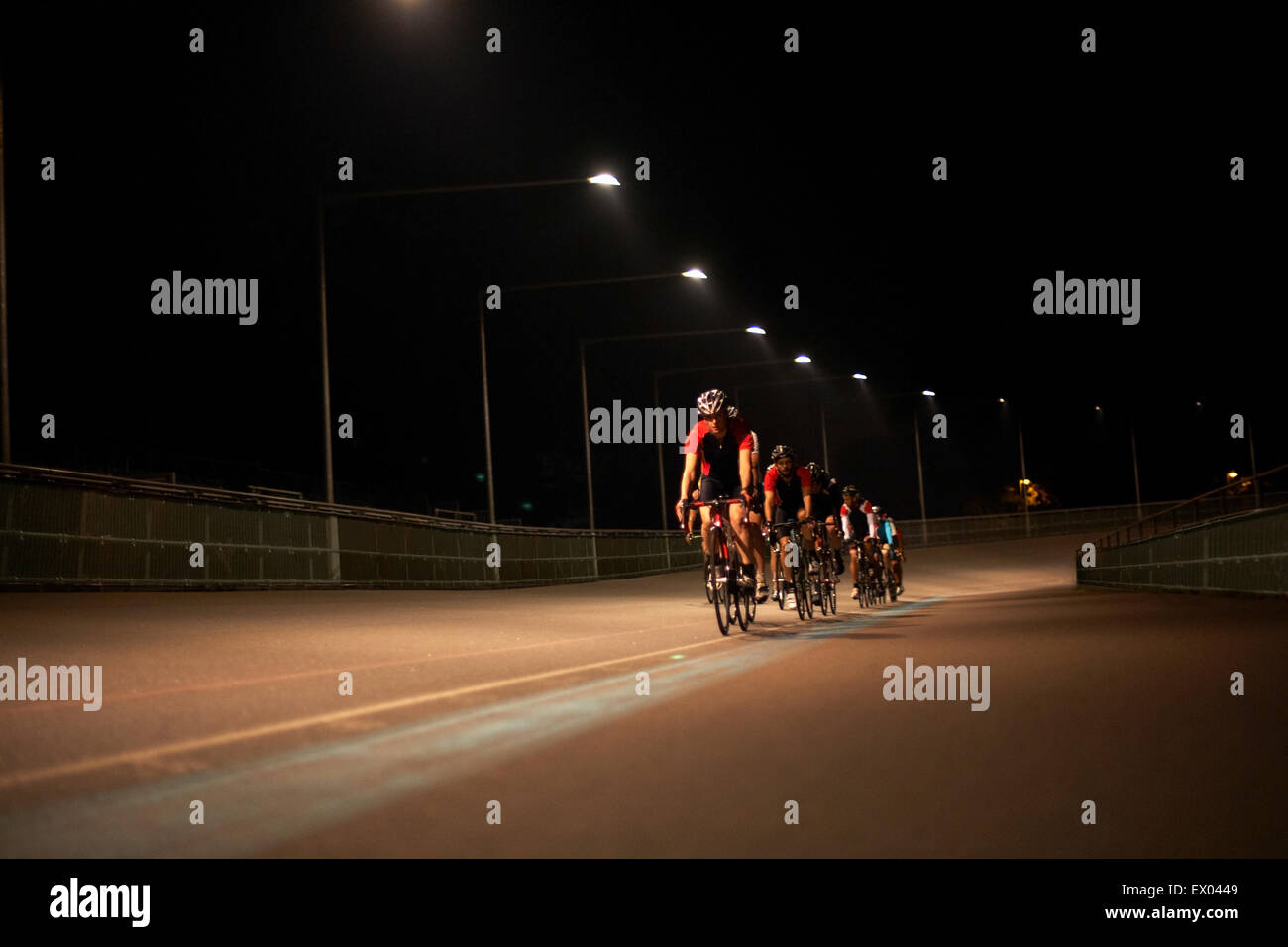 Cyclists cycling on track at velodrome, outdoors Stock Photo