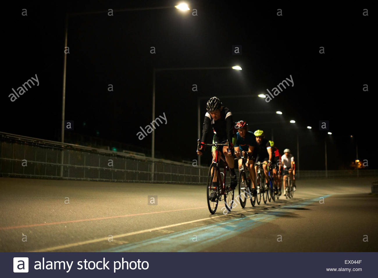 Cyclists cycling on track at velodrome, outdoors - Stock Image