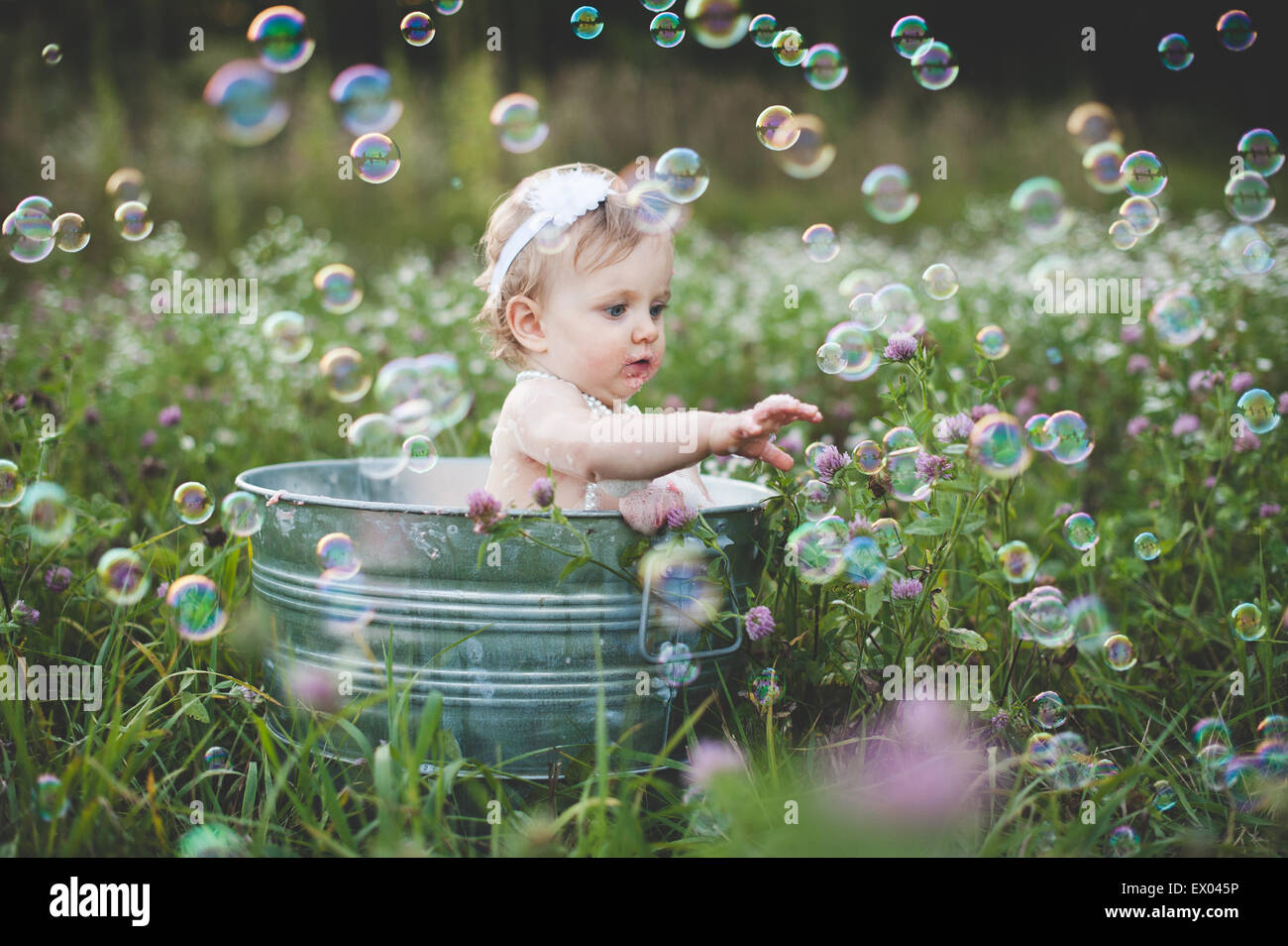 Baby girl in tin bathtub in meadow reaching for floating bubbles - Stock Image
