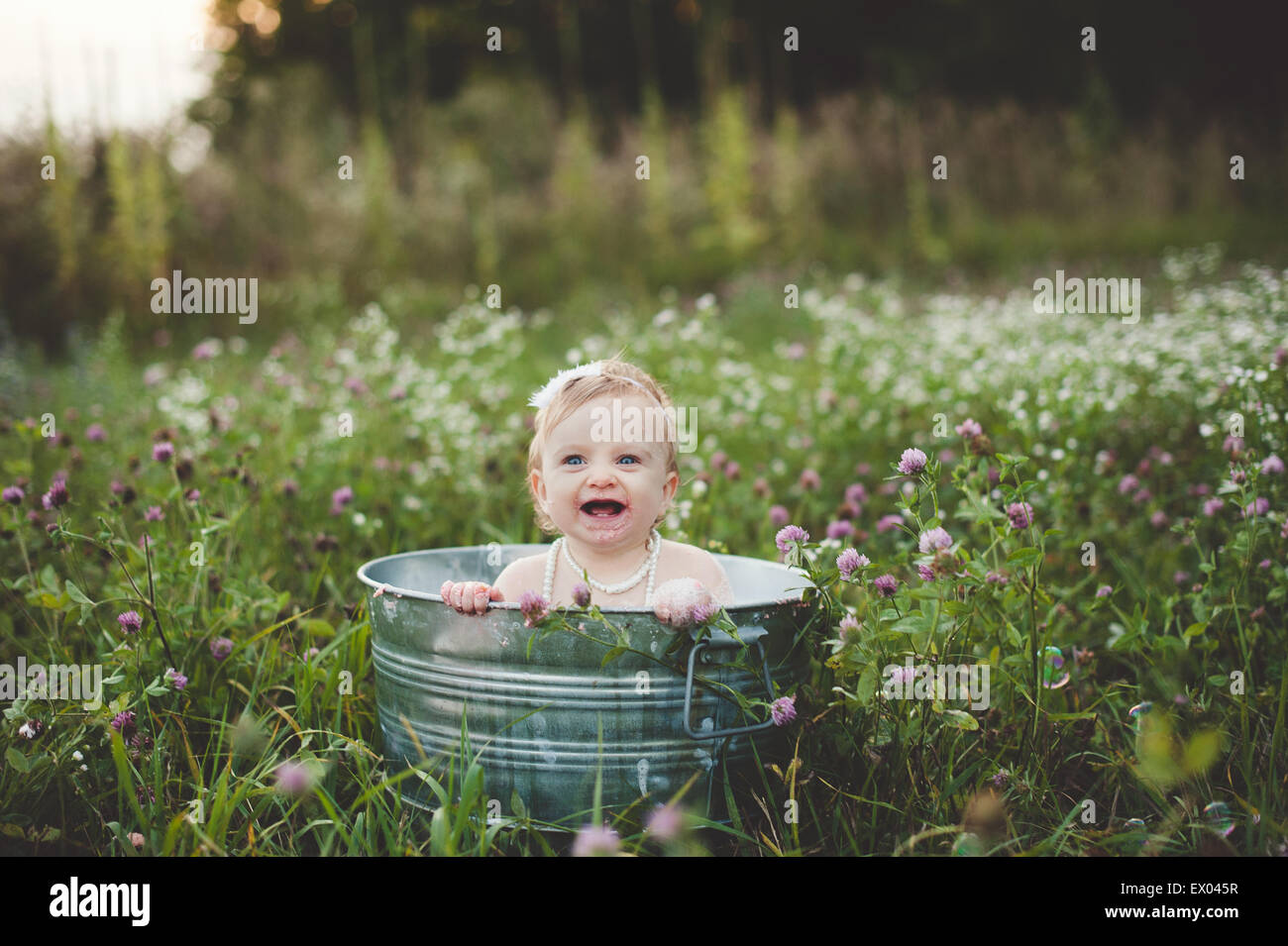 Baby girl bathing in a tin bathtub in a wild flower meadow Stock Photo
