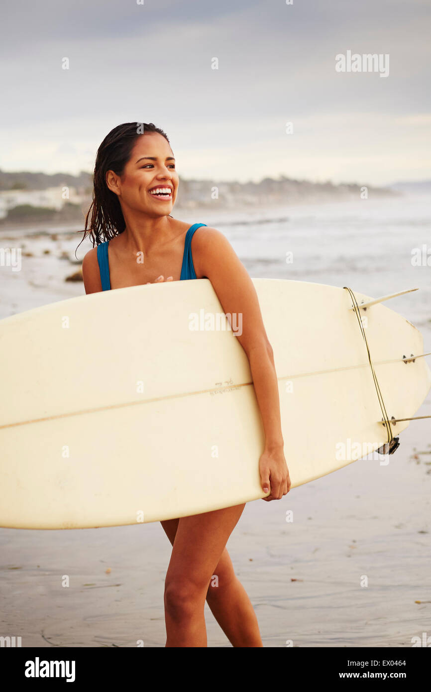 Young woman strolling on beach carrying surfboard, San Diego, California, USA - Stock Image